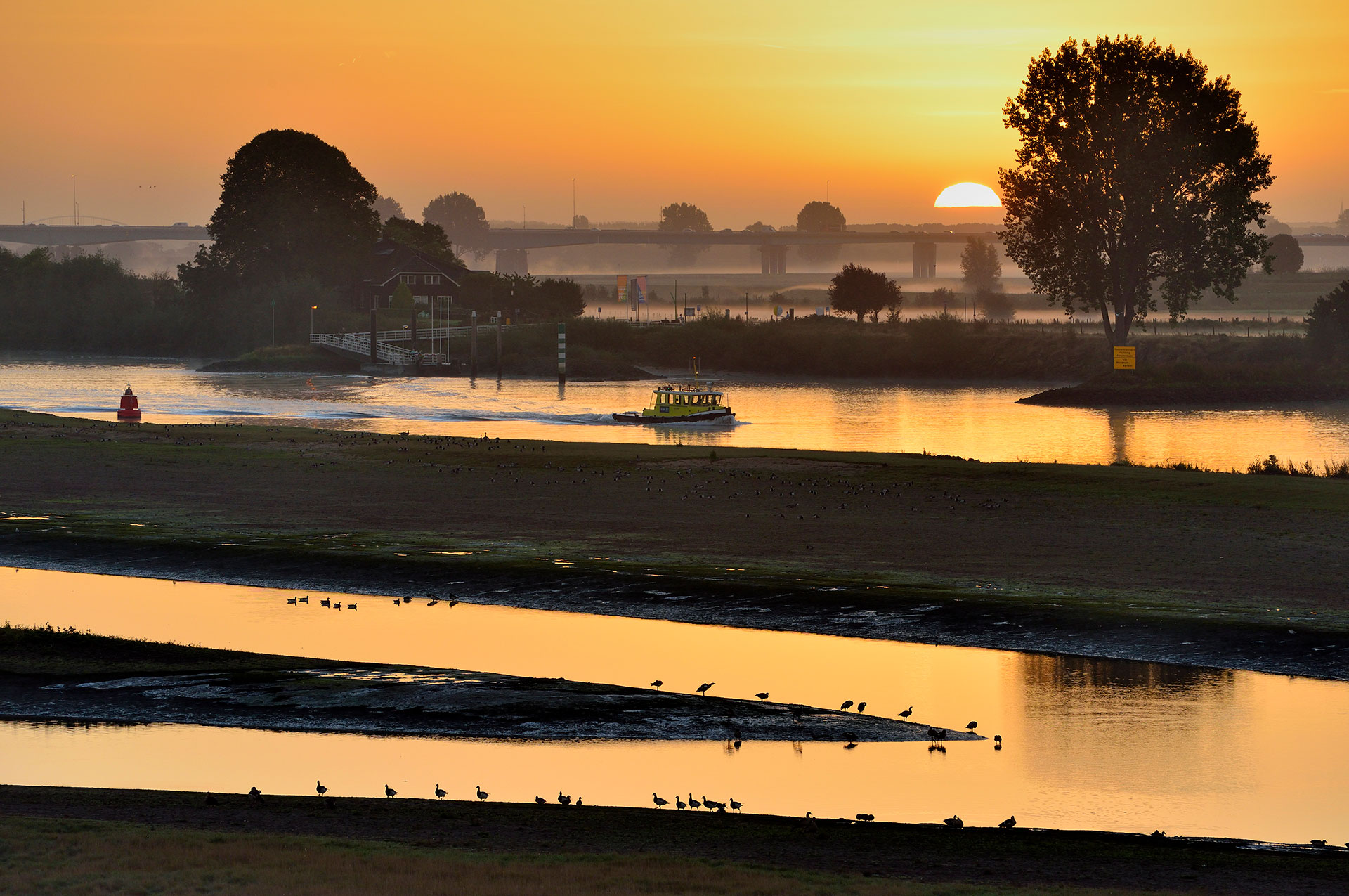 The river Lek at Nieuwegein at sunrise with ship and ferry