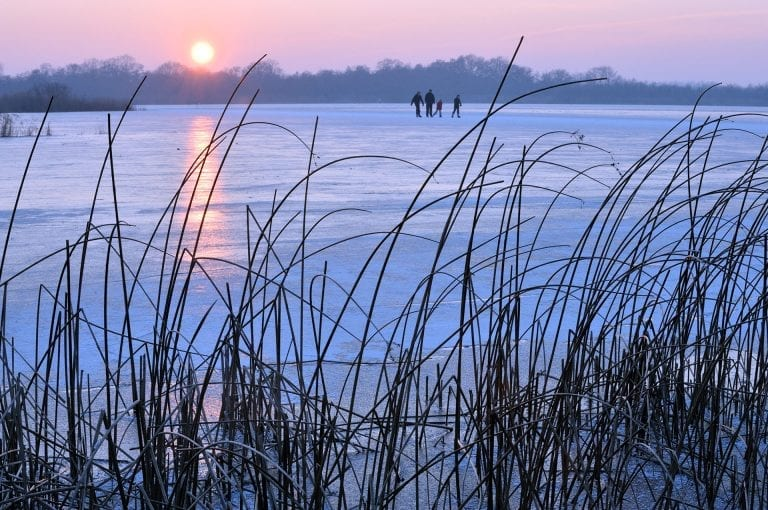 A family of ice skaters on the Ankeveense Plassen at sunset