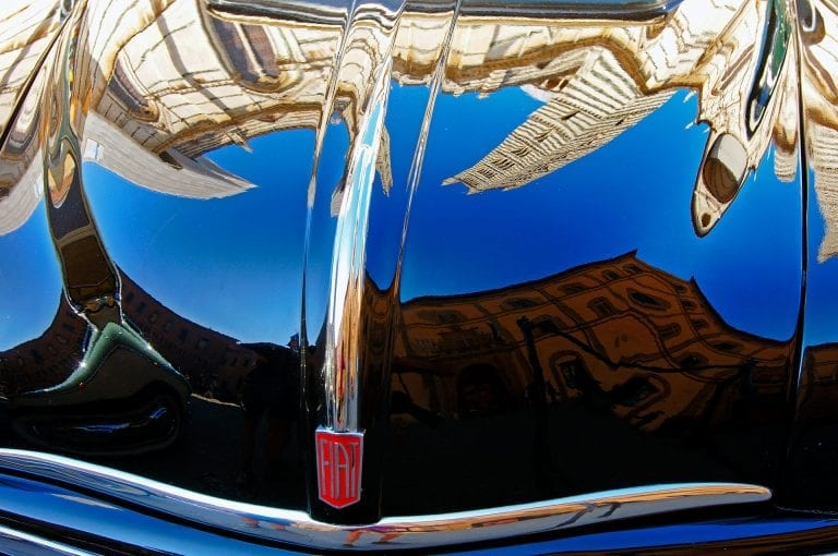 The Siena Cathedral mirrored in the bonnet of a classic Fiat car.